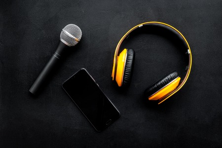 Podcast record with mobile phone, microphone and headphones on black office desk background top view space for text Stock Photo
