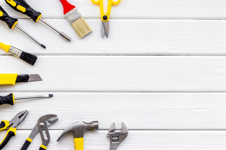 Building, painting and repair tools for house constructor work place set on wooden white background top view space for text