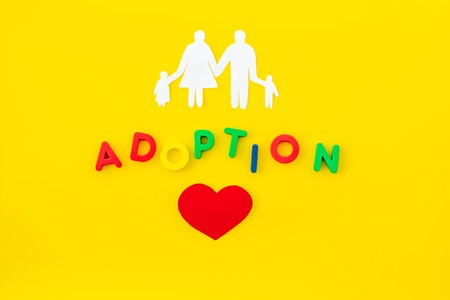 Family and adoption copy on yellow table background top view