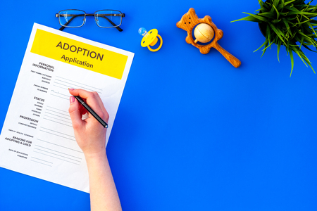 Application form for adopt child on blue table background top view mock up
