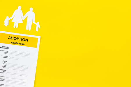Adoption application near family figures on yellow table background top view copyspace