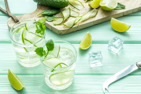 Summer cocktails for freshness with lime, cucumber and ice on mint green wooden table background