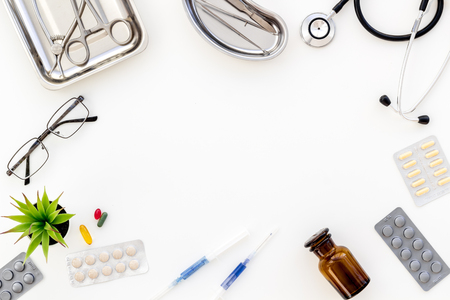 Pills and instruments of doctor for cure in hospital frame on white background top view copyspace