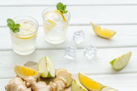 Fresh drink with apple, orange and ice on white table background Imagens