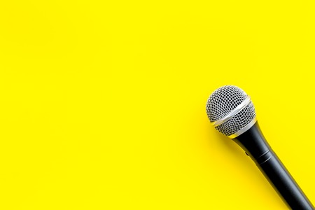 Blogger, journalist or musician office desk with microphone on yellow studio background top view copyspace