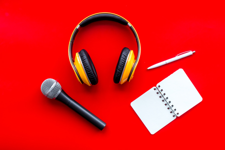 Record studio set. Blogger, journalist or musician work space with microphone, notebook and headphones on red background top view mock up