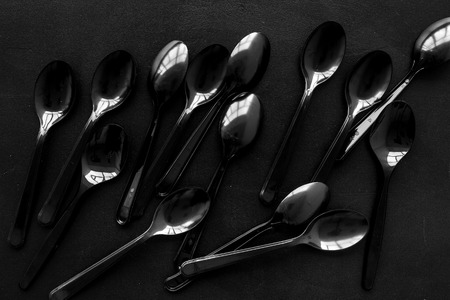 Plastic flatware for eco concept on black background top view pattern. Zdjęcie Seryjne