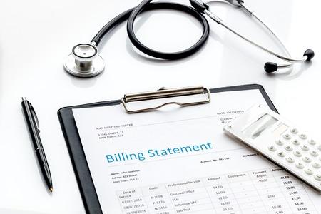 Medical treatment bill and phonendoscope on white desk background