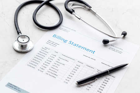 Arztrechnung und Phonendoskop auf weißem Schreibtischhintergrund