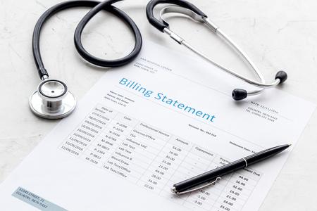 Medische behandelingsrekening en phonendoscope op witte bureauachtergrond