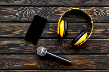 Blogger, journalist or musician work with microphone, telephone and headphones on wooden background top view mockup