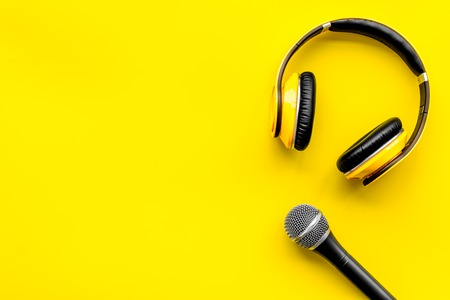 Blogger, journalist or musician work space with microphone and headphones on yellow background top view space for text