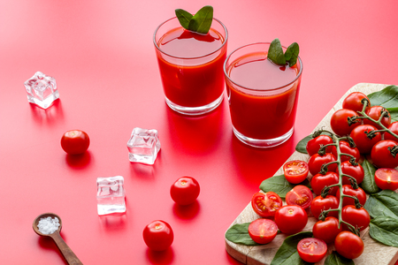 Fresh drink with tomato, spinach and ice on red background Imagens