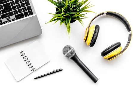 Blogger, journalist office with laptop, notebook, microphone and headphones white background top view copyspace