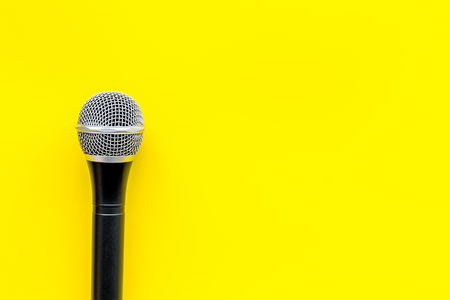 Blogger, journalist or musician work space with microphone on yellow background top view space for text