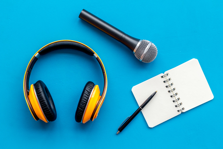 Blogger, journalist or musician office desk with notebook, microphone and headphones on blue studio background top view copyspace Stock Photo