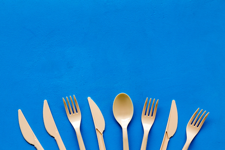 Eco and plastic utilization concept with flatware on blue background top view mock up