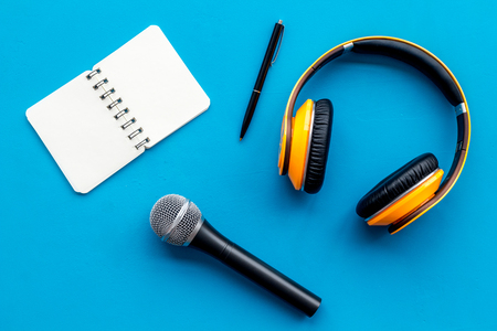Microphone, headphones, notebook for blogger, journalist or musician work on blue office desk background top view mockup