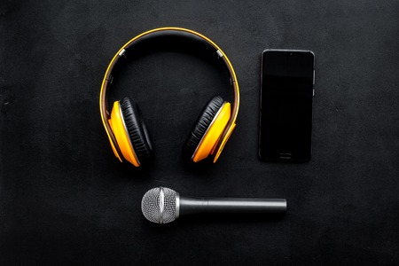 Record studio set. Blogger, journalist or musician work space with microphone, mobile telephone and headphones on black background top view mockup Stock Photo