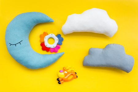 Baby care concept. Baby sleep pattern with moon pillow, cloud, feeding bottle and toy on yellow background top view Stock Photo