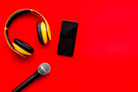 Microphone, headphones, mobile phone for blogger, journalist or musician work on red office desk background top view mockup Stock Photo