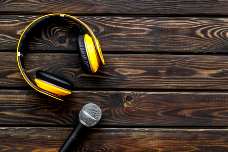 Podcast record with microphone and headphones on wooden office desk background top view space for text