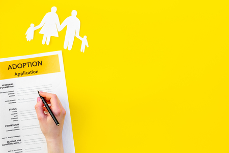 Children care and motherhood set with adoption application and family paper figure on yellow background top view space for text Stock Photo