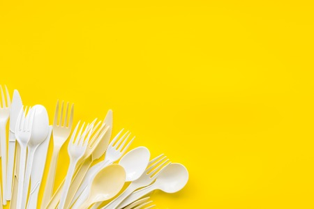 Eco and plastic utilization concept with flatware on yellow background top view mock up