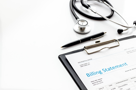 Medical treatment bill and phonendoscope on white desk background Stock Photo - 120392145