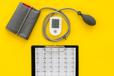 Tonometer cardiogram for heart diseases diagnostic on yellow desk background top view