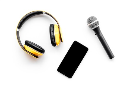 Record studio set. Blogger, journalist or musician work space with microphone, mobile telephone and headphones on white background top view mockup Stock Photo