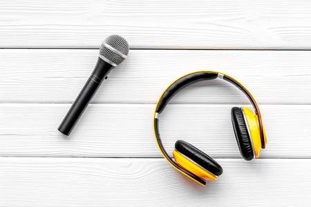 Podcast record with microphone and headphones on white wooden office desk background top view Stock Photo