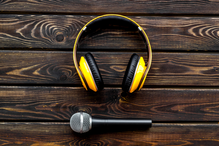 Microphone, headphones for blogger, journalist or musician work on wooden office desk background top view