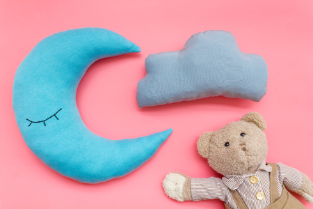 Baby care concept. Baby sleep pattern with moon pillow, cloud, teddy bear on pink background top view Stock Photo
