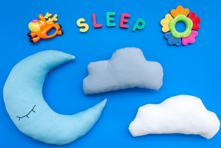 Baby care concept. Sleep copy for baby pattern with moon pillow, cloud, toy on blue background top view Stock Photo