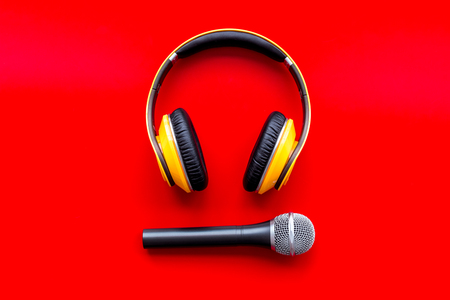 Podcast record with microphone and headphones on red office desk background top view Stock Photo