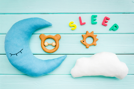 Baby care concept. Sleep copy for baby pattern with moon pillow, cloud, toy on mint green wooden background top view