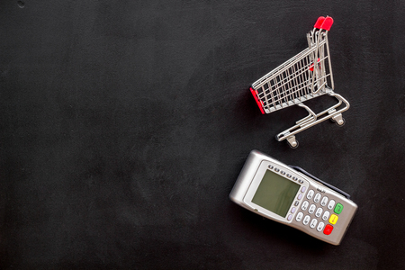 Online shopping concept with trolley and card machine for payment on black background top view space for text