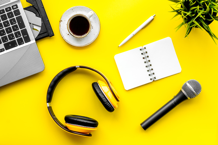 microphone, headphones, notebook and laptop for blogger, journalist, musician work yellow background top view copyspace