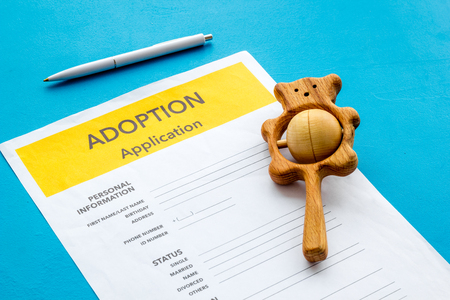 Application to adopt child with toy on blue background Stock Photo