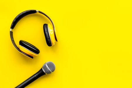 Blogger, journalist or musician office desk with microphone and headphones on yellow background top view copyspace
