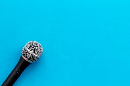 Microphone for blogger, journalist or musician work on blue background top view mock-up