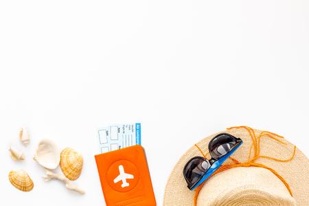 Sombrero de paja, gafas de sol, pasaporte con boletos, conchas para vacaciones en el mar en maqueta de vista superior de fondo blanco