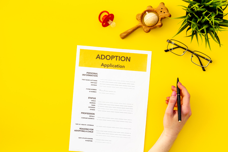 Family and adoption child concept with application, dummy, toy, glasses on yellow table background top view