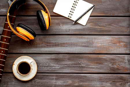 Professional dj instruments on workdesk with headphones, guitar, notebook and coffee on wooden background top view mockup Foto de archivo