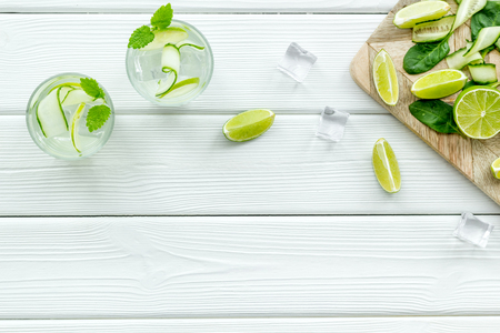 Fresh drink with lime, mint, cucumber and spinach on white table background top view mockup