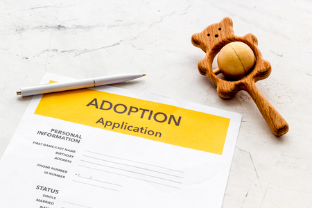 Children care with adoption application and toy on white office table background