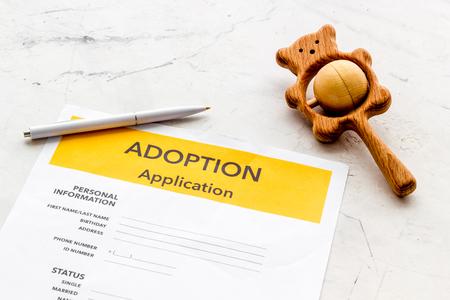 Kinderbetreuung mit Adoptionsantrag und Spielzeug auf weißem Bürotischhintergrund