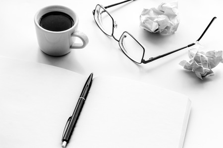 Work desk of writer with notebook, glasses, coffee on white desk background mock up