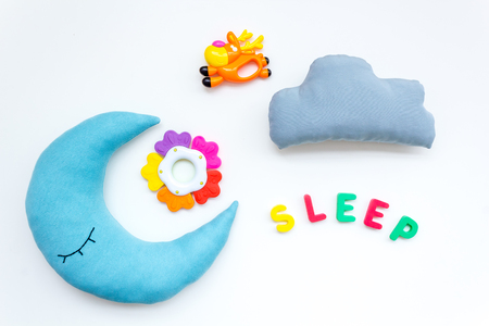 Baby care concept. Sleep copy for baby pattern with moon pillow, cloud, toy on white background top view Stock Photo